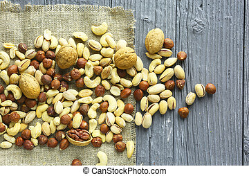 Assortment of nuts on a dark wooden table. View from above