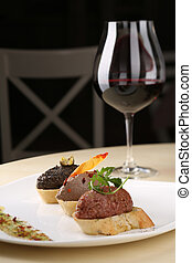 Assortment of pate canapes bread on white plate with glass red wine, dark background