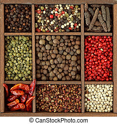Assortment of peppercorns and chili in wooden box
