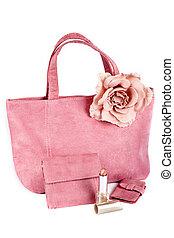 Assortment of pink handbags and lipstick