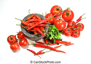 Assortment of red peppers and tomatoes on white