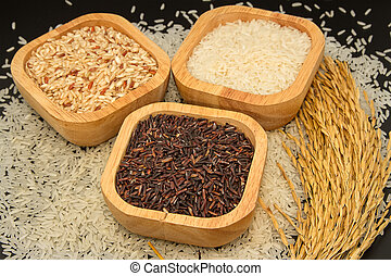 Assortment of rice in wooden bowl with paddy rice