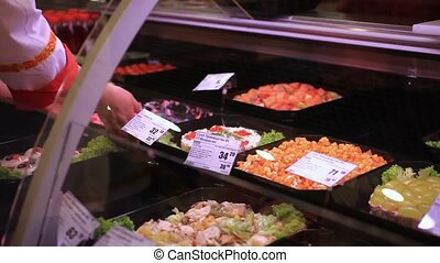 assortment of salads on display cabinet in supermarket. Female hands saleswoman puts salad for sale. HD. 1920x1080