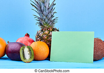 Assortment of tropical fruits and blank paper card. Group of...