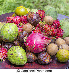 Assortment of tropical fruits - green mango, avocado,...