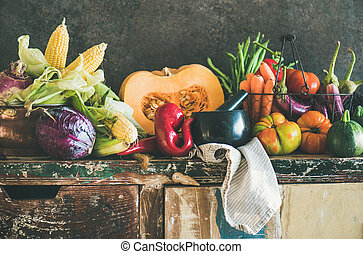 Assortment of various Fall vegetables for cooking on rustic cupboard