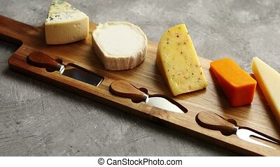 Assortment of various kinds of cheeses served on wooden...