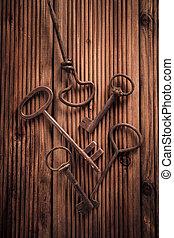 Assortment of vintage keys on wooden background