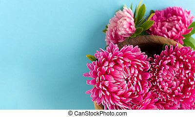 Asters gathered in wooden bowl. Copy space