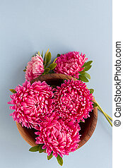 Asters gathered in wooden bowl. Copy space.