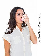 Asthmatic brunette using her inhaler