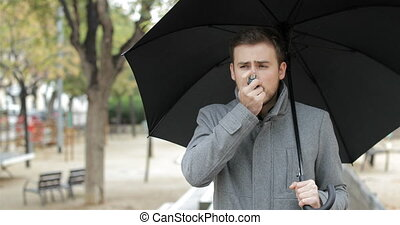 Asthmatic man using an asthma inhaler under the rain - Front...