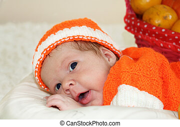 Astonished cute newborn baby dressed in a knitted orange costume