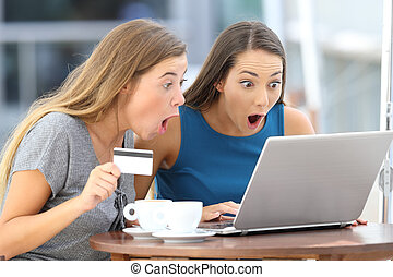 Astonished friends buying on line in a bar - Two astonished...