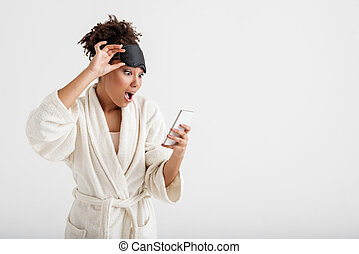Astonished girl in coat using cellphone