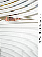 Astonished male eyes spying through roller blind - ...