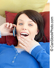 Astonished teen girl talking on phone lying on a sofa