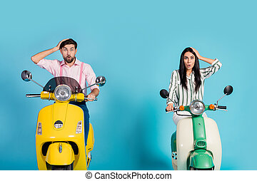 Astonished two bikers man woman travel yellow green motor bike get unbelievable idea they get lost impressed touch hands head scream wow omg isolated over blue color background