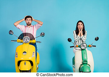 Astonished two bikers ride yellow green electric scooters impressed by idea man woman she he get lost scream omg unbelievable wear formalwear clothes isolated over blue color background
