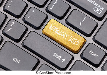 Astrology 2019 on golden enter key, of a black keyboard.