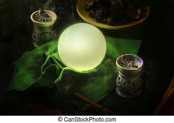 Crystal ball to guess the future, on a divination table.