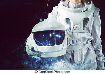 Astronaut in a spacesuit holding helmet in his hand. Close-...