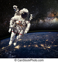 Astronaut in outer space above the earth during night time....