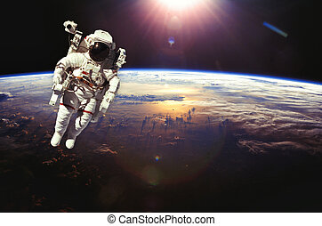 Astronaut in outer space above the earth during sunset. Elements of this image furnished by NASA.
