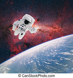 Astronaut in outer space with planet earth as backdrop. Elements of this image furnished by NASA.