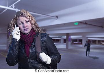 asustado, mujer joven, en, teléfono celular, en, estacionamiento, estructura