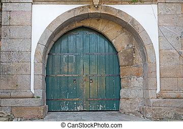 asymmetric antique wooden door on stone frame
