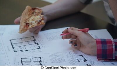 At a desk a woman and a man with a pizza look floor plan on paper.