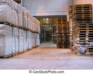 A corridor in a warehouse, with pallets of white boxes on the left side, and a stable of empty pallets on the right side.
