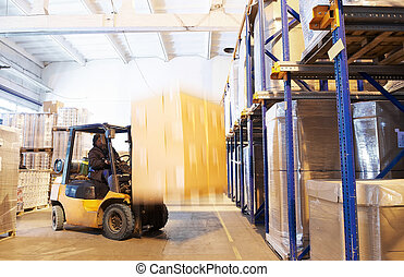 at a warehouse with forklift loader - worker driving a ...
