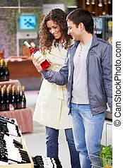 At a wine choice - The young couple chooses wine in shop