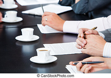 At conference - Image of businesspeople?s hands with pens,...