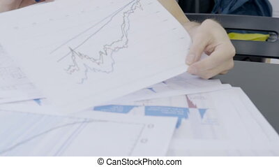 At desk man analyzes data, which are depicted on different...