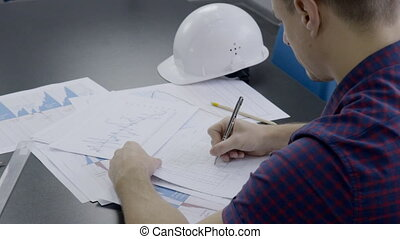 At desk there is an engineer working on a construction...