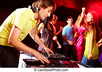 At disco - Smart deejay spinning turntables with dancing...