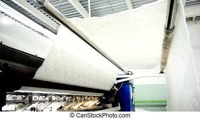 At garment factory a white linen for upholstery of furniture is woven.
