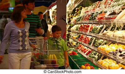 A family of four approaching vegetable row in the supermarket, taking some vegetables and placing them into the trolley