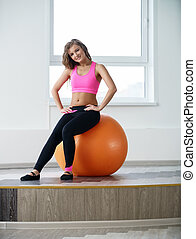 At gym. Pretty girl posing sitting on fitness ball