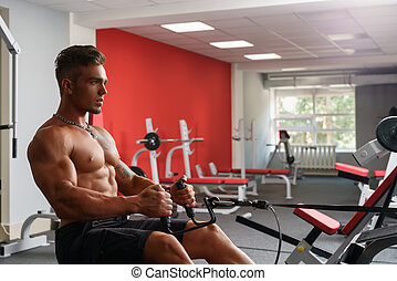 At gym. Sexy shirtless guy exercising on simulator