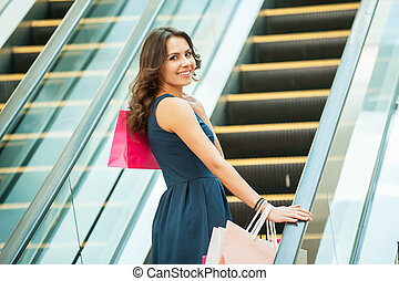 At her way to the next store. Rear view of beautiful young woman with shopping bags on mall escalator