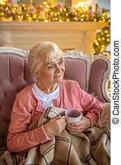 Senior woman sitting on a sofa with a cup of tea