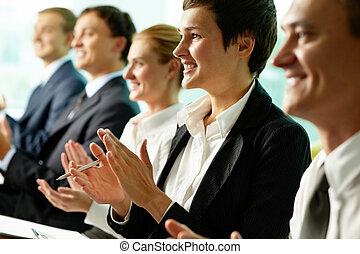 At lecture - Business people sitting in a row and applauding...