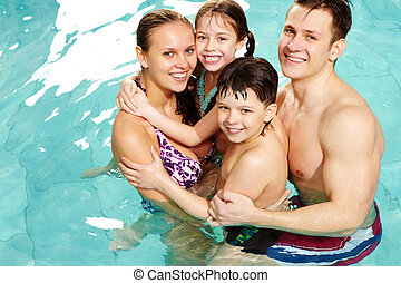 Cheerful family in swimming pool smiling at camera