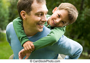 At leisure - Image of happy man holding his son while having...