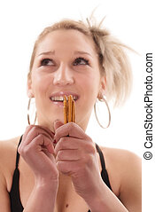 At leisure - Young woman eating cinnamon sticks, focus on...