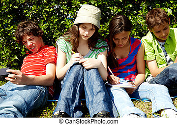 At leisure - Portrait of friendly teens sitting on green...